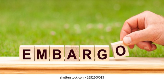 Word Embargo written with wooden blocks. Man hand holding wooden cube block with Embargo business word on green lawn background