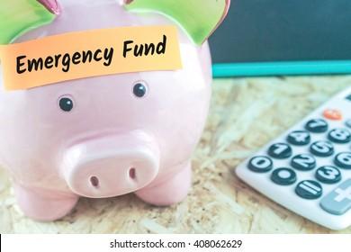 word emergency fund on note paper on blurred pink piggy bank on calculator blackboard background