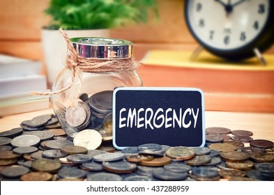 Word Emergency on mini chalkboard and coin in the jar with blurred background of books, green plant and clock. Financial Concept.