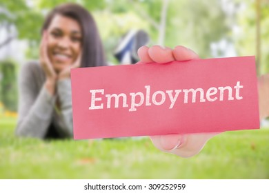 The word employment and hand showing card against pretty brunette smiling at camera in park