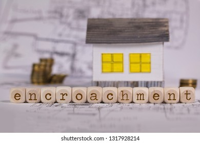 Word  ENCROACHMENT composed of wooden letters. Small paper house in the background. Closeup