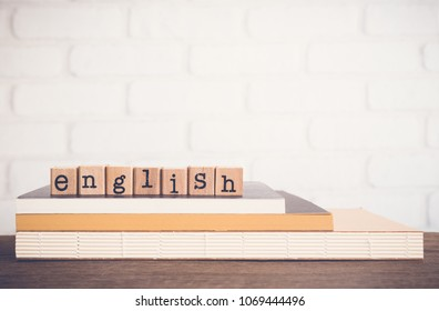 The word English, text on wooden cubes on top of books. Background copy space, vintage minimal style. Concepts of language learning, course training or business of education .