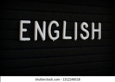 The word English in white plastic letters on a notice board