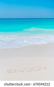 Word Enjoy handwritten on sandy beach with soft ocean wave on background