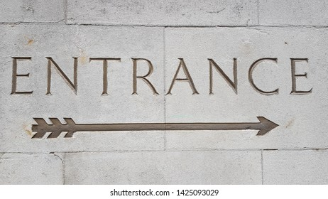 The word Entrance carved in white stone blocks and an arrow underneath pointing left to right.