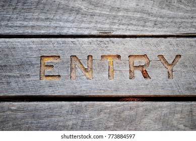 The word 'entry' is carved in wood