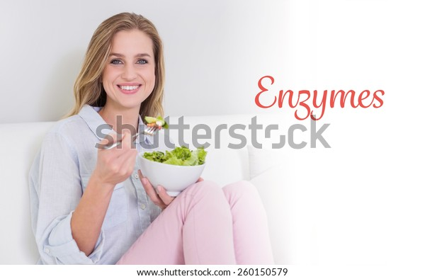 The word enzymes against smiling casual blonde sitting on couch holding salad bowl