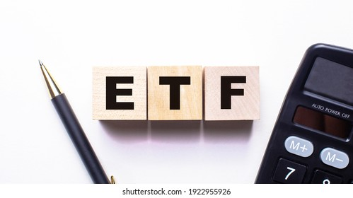 The word ETF Exchange Traded Funds is written on wooden cubes between a pen and a calculator on a light background.