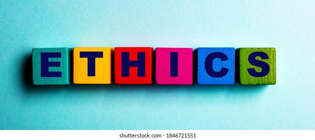 The word ETHICS is written on multicolored bright wooden cubes on a light blue background