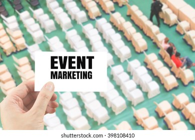 word event marketing on white card in hand on blurred rows of chair background