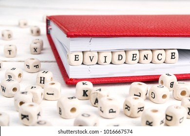 Word Evidence written in wooden blocks in red notebook on white wooden table.