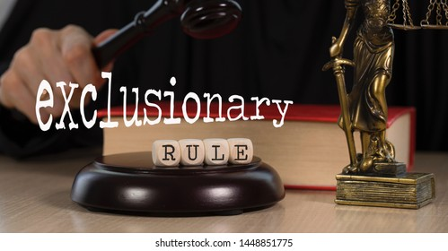 Word EXCLUSIONARY RULE composed of wooden dices.  Wooden gavel and statue of Themis in the background. Closeup