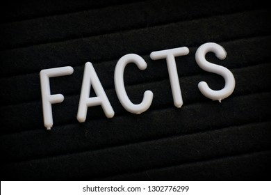The word Facts in white plastic letters on a notice board