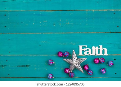 The word Faith hanging on antique rustic teal blue wooden background with colorful turquoise and pink Christmas ornaments and silver star;  religious holiday and spiritual wood sign with copy space