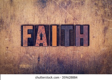 "The word ""Faith"" written in dirty vintage letterpress type on a aged wooden background."