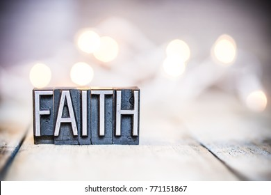 The word FAITH written in vintage metal letterpress type on a bokeh light and wooden background.