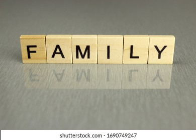 the word family is made up of square wooden letters on a gray background