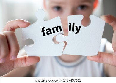 Word family on two puzzles. the child is holding two white puzzles. Family concept. Parents' divorce. Family breakdown