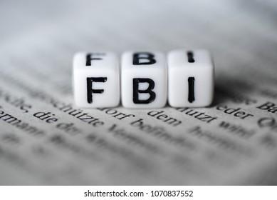 Word FBI formed by wood alphabet blocks on newspaper