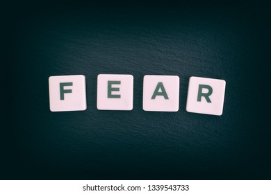 Word Fear on a black slate background. Close up.