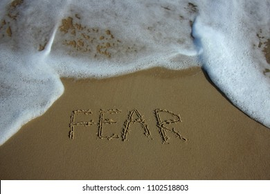 """The word """"fear"""" is washed off by sea waves. Concept: treatment of phobias, getting rid of fear, psychological help, psychotherapy."""