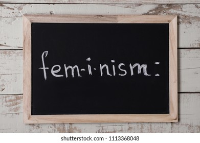 "The word ""feminism"" written on blackboard. Women's rights concept. Feminism movement"