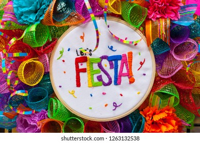 The word `fiesta` stitched in colorful letters on multicolored mash decorated with ribbons, glitter and paper flowers. Decoration for Fiesta Festival.