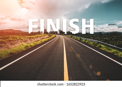 The word finish behind the tree of empty asphalt road at golden sunset and beautiful blue sky.