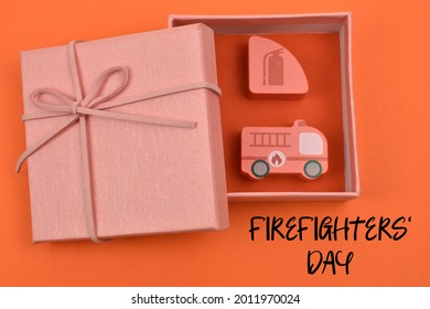 The word Firefighter's  Day and the gift box inside there are wooden blocks in the shape of fire extinguishers and fire vehicles.