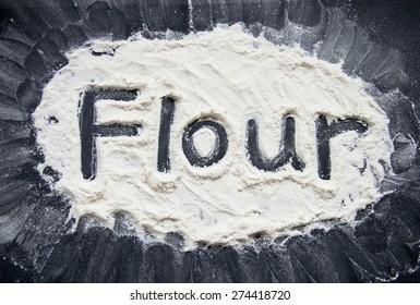 Word Flour Written on Flour on Black Background