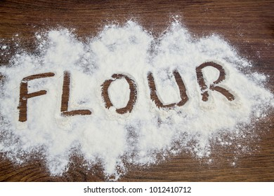 Word flour written on table. Wheat flour scattered on the table.