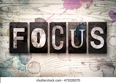 "The word ""FOCUS"" written in vintage dirty metal letterpress type on a whitewashed wooden background with ink and paint stains."
