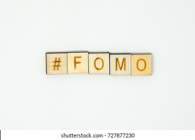 The word #FOMO (hashtag FOMO) spelled out in wooden alphabet tiles on an isolated white background. FOMO is an acronym meaning Fear of Missing out and used on social media by youths and millennials