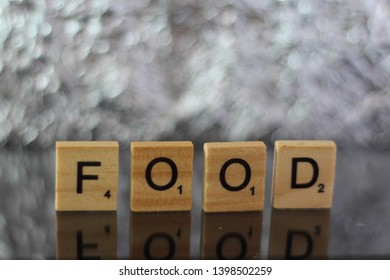 Word FOOD written with Scrabble letters isolated in studio shot setup. Editorial image, close up photo, macro photography. Illustration of world hunger problems and feeding poor people.
