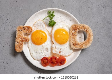 Word food written with toast letters fried eggs