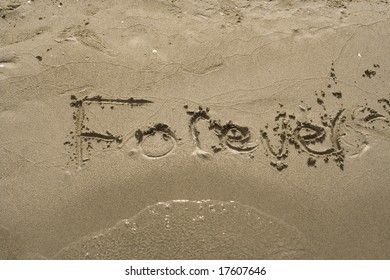 The word forever is written in sand and partially washed away.