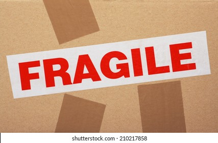 The word Fragile on sticky packaging tape fixed to a cardboard box