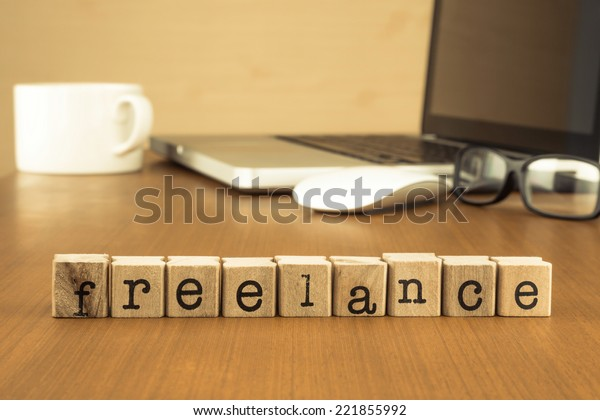 The word freelance on wood stamp stacking on desk with laptop, glasses and a cup of coffee at home office, vintage retro image style