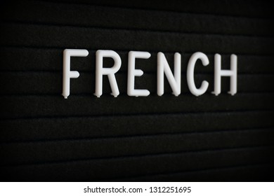 The word French in white plastic letters on a black notice board