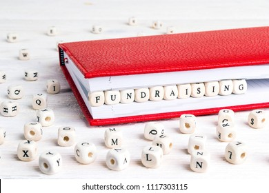 Word Fundraising written in wooden blocks in red notebook on white wooden table. Wooden abc.
