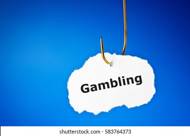 The word Gambling on a piece of paper on fishing hook over blue background. Conceptual image about the risk of addiction to gambling.