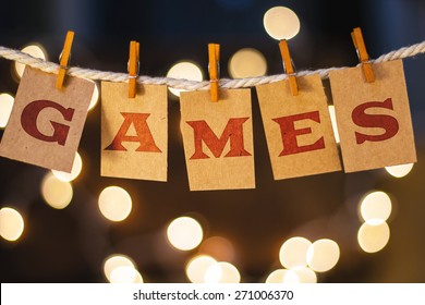 The word GAMES printed on clothespin clipped cards in front of defocused glowing lights.