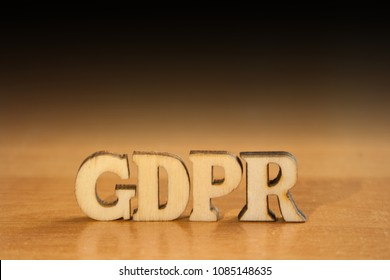 The word 'gdpr' made of wooden letters. wood inscription on table and dark black background
