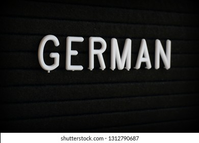 The word German in white plastic letters on a black notice board
