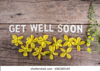 The word 'GET WELL SOON' with spring flowers on wooden background.