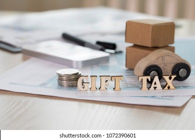 Word GIFT TAX composed of wooden letters. Coins, papers, pen, wooden car, carton boxes in the background. Closeup