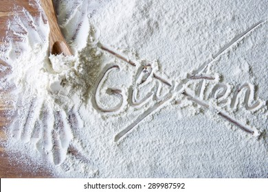 Word gluten crossed out on wood board with flour
