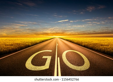 The word GO written on highway road in the middle of empty asphalt road at golden hour sunset. Concept for success.