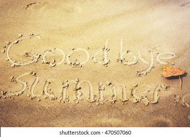 word Goodbye summer written on the sand, yellow leaf. sun light effect