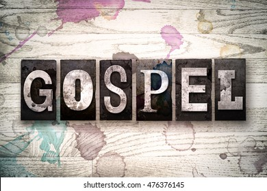 "The word ""GOSPEL"" written in vintage, dirty metal letterpress type on a whitewashed wooden background with ink and paint stains."
